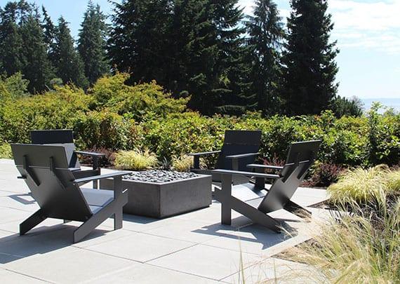 moderne gartengestaltung mit gartenterrasse aus rechteckigen steinplatten und sitzgruppe aus schwarzen gartensesseln und moderner Feuerschale aus metall