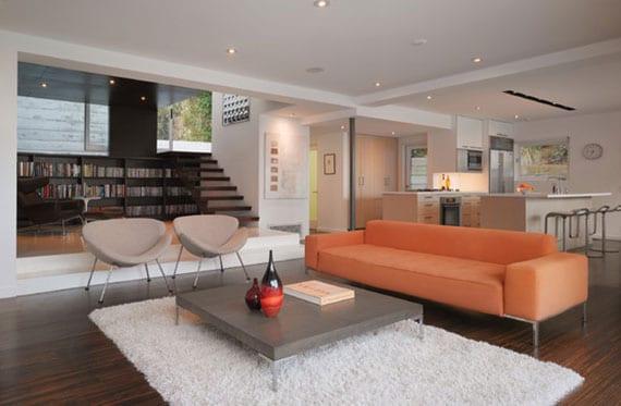attraktive einrichtungsidee für offene wohn-esszimmer mit moderner küche, offener innentreppe holz, leseecke mit schwarzem bücherregal und panoramafenster, moderne sofa orange und beton couchtisch auf dunklem parkettboden
