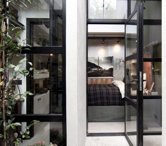 tolle schlafzimmer idee für kleinen schlafbereich mit tür zum kleinen garten im verglasten atrium
