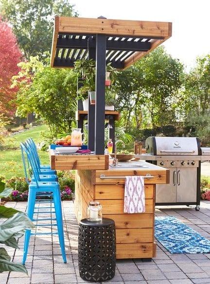 bunte und attraktive gartengestaltung mit terrasse aus pflastern, gartenbar mit waschbecken und vintage-barhockern blau, rundem beistelltisch schwarz und gartengrill
