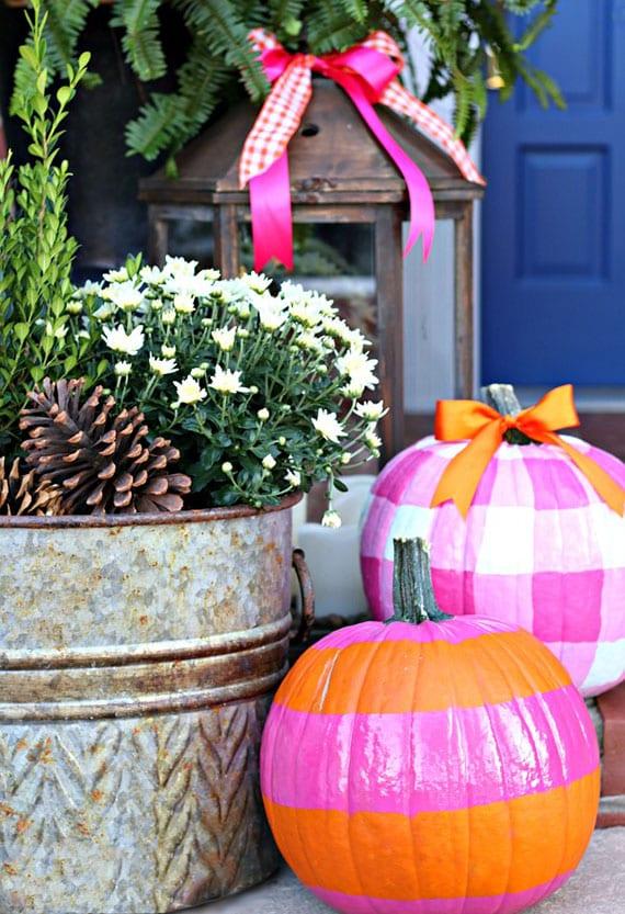 originelle herbstdeko idee mit rosafarbigen kürbissen und vintage metalleimer gefüllt mit zapfen und weißen chrysanthemen