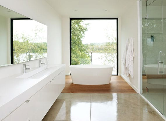 stilvolle gestaltung in weiß für moderne und großzügige badezimmer mit panoramafenster, freisteheneder badewanne auf holzboden und duschbereich hinter glaswand