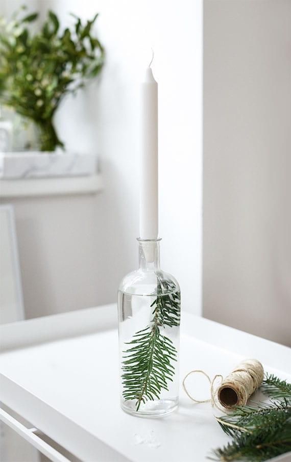 einfache bastelidee für originellen diy kerzenhalter aus glasflasche mit nadelbaumzweig und wasser als tolle advent deko idee