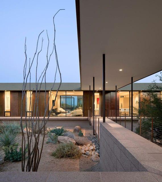 modernes haus mit flachdach, überdachtem hauseingang, großen fenstern mit schiebeelemente aus metal und attraktivem steingarten