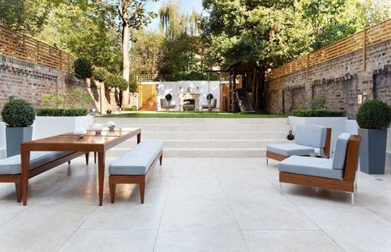 hofgarten modern gestalten mit terrasse aus weißen fliesen, holzgartenmöbeln, lounge-bereich mit außenkamin auf gras, grauen pflanzenkübel mit kugel-buchsbäumen und ziegelmauer