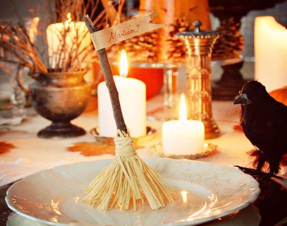 tisch zu halloween decken mit kerzen, reben und hexenbesen-platzkarten