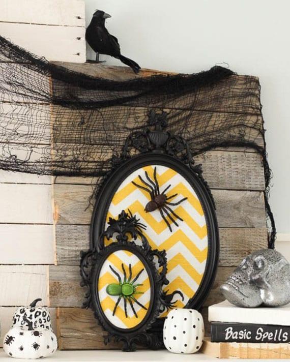 originelle bastelidee für halloween mit schwarzen vintage-bilderrahmen oval, chevron stoff in gelb und weiß, plastikspinnen, weißen kürbissen, wandtafel aus holzbrettern, schwarzem netz und rabe
