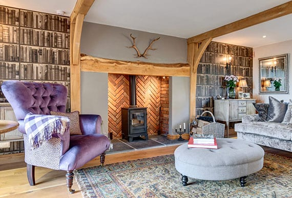 gemütliches wohnzimmer im landhausstil mit rustikalem kamin, sichtbarer holztragkonstruktion, moderner fototapete-wandgestaltung, akuentwand aus ziegeln und barock-moblierung