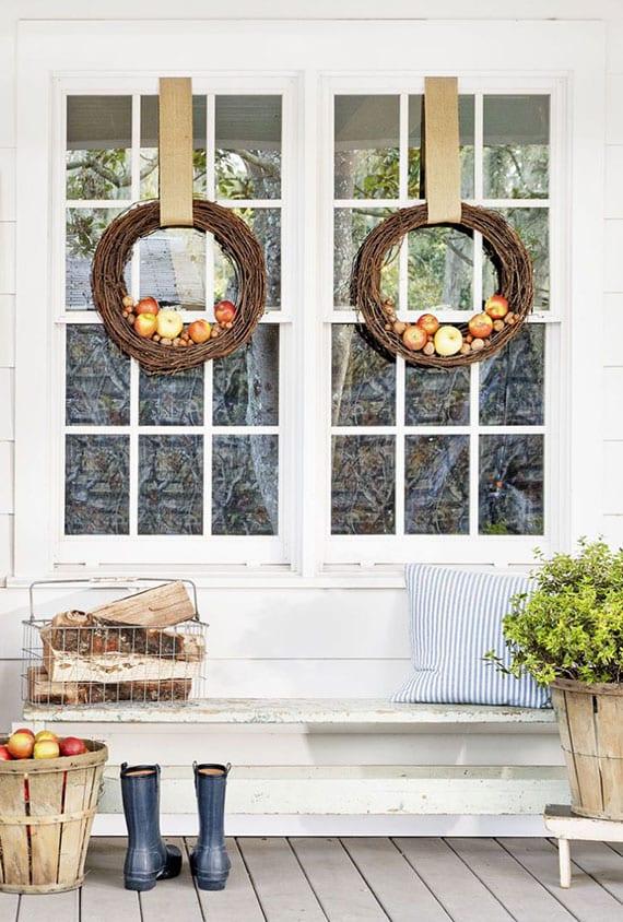veranda und fenster herbstlich dekorieren mit feuerholz, rustikalen holzkörben und weinreben-Kranz mit äpfeln