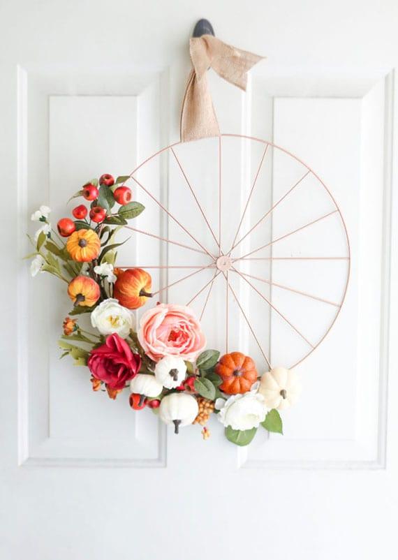 schicke herbstdeko haustür mit diy kranz aus metallrad, kleinen kürbissen und großen blumen mit frünem laub
