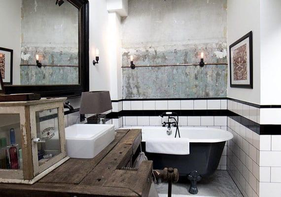 attraktives badezimmer design im industriellen stil mit altem Hobelbank-Waschtisch, schwarzer badewanne, weißen und schwarzen badfliesen, badspigel im schwarzen rahmen und nackter akzentwand mit vintage lampen