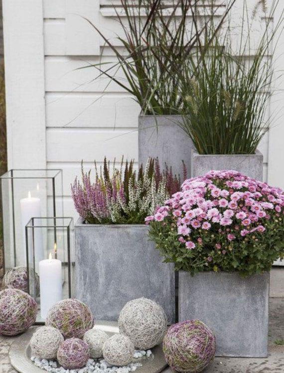 balkon effektvoll und modern dekorieren mit Kerzen in Glaskerzenhalter, Ziergräsern und rosafarbigen Chrysanthemen in beton Blumenkübeln