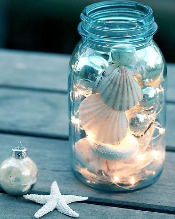 coole sommerdekoidee und kreative bastelidee für diy glas-laterne mit lichterkette, kleinen christbaumkugeln silber und weißen seeschnecken