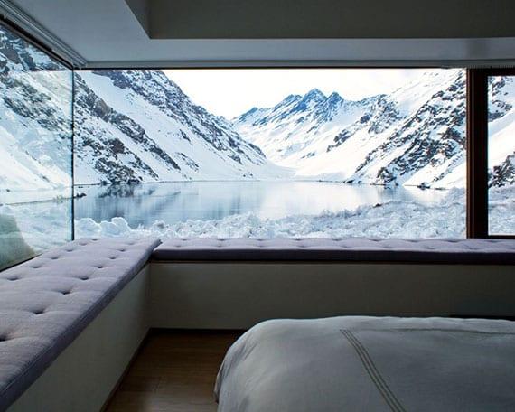 modernes schlafzimmer interieur mit sitzbänken entlang panoramafenstern mit blick auf see und gebirge im winter