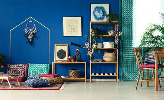 coole wohnzimmergestaltung im boho wohnstil mit wandfarbe blau,gardinen in türkis,holzregalen mit pflanzen in weidenkörben, sitzecke am boden aus ethno gemusterten kissen und teppich