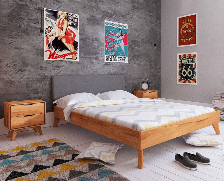 modernes schlafzimmer interieur design mit grauem akzentwand in zementoptik, retro-postern, holzboden weiß, bunt gemustertem teppich, holzmöblierung und gemusterter bettwäsche weiß für modernes bett mit bettkopfteil grau
