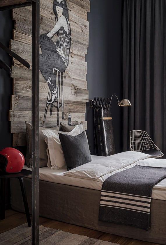 coole schlafzimmer einrichtungsidee mit diy bett-kopfteil aus paletten, wandfarbe schwarz, metall-garderobe, vintage-wandlampe, coole schlafzimmer deko und bettbezug grau