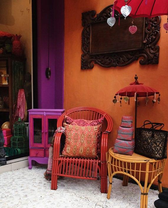 auffälige farbgestaltung und raumgestaltung im boho stil mit wandfarbe orange, rattanstuhl rot, vintage-holzmöbel in lila und wanddeko in dunkelholz