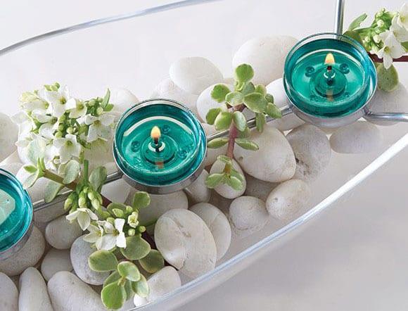 moderne tischdeko ideen mit blauen teelichten, weißen steinen und grünes in glasschale
