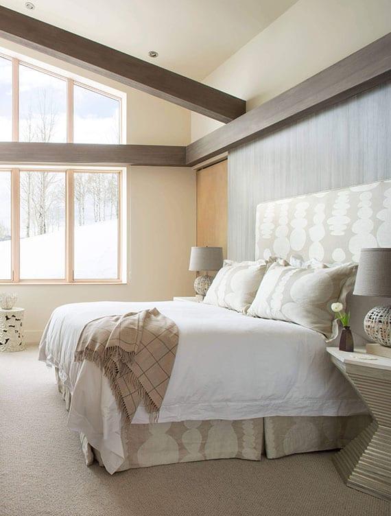 modernes schlafzimmer interieur in beige, weiß und dunkelholz mit holzwandverkleidung hinter boxspringbett, spiralförmigen nachttischen mit tischlampen grau und teppichboden beige
