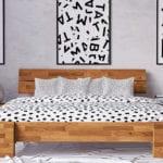 attraktives schlafzimmer design mit doppelbett aus massivholz mit holzkopfteil,betonwand mit buchstabe-postern in schwarzen bilderrahmen und bettwäsche weiß mit dalmatiner-muster