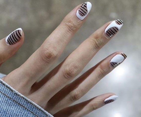 originelle nagelkunst mit schwarzen streifen und weißem nagellack