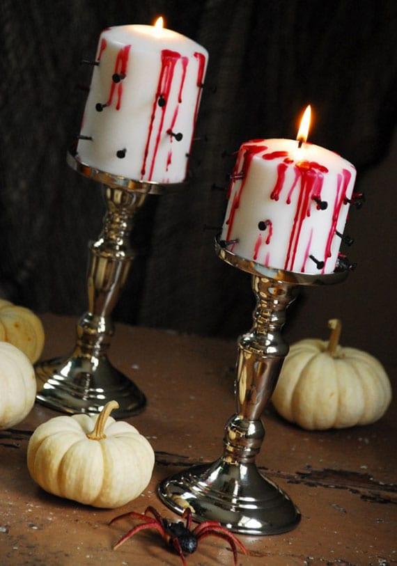 einfache bastelidee für diy kerzendeko zu halloween mit schwarzen Senkkopf-Nägeln und rotem Wachs als gruselige tischdeko