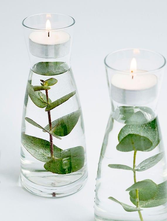 coole deko im glas selber machen mit teelichtkerzen und grünen zweigen in glasvasen mit wasser