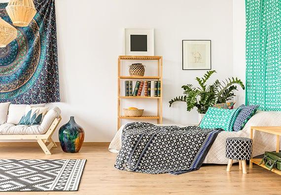 coole gestaltungsidee für ein gemütliches wohnzimmer im boho wohstil mit ethno gemustertem wanteppich blau, rattan-lampen,modernem soga holz, gardinen türkis, teppich in schwarzweiß und bilderrahmen wanddeko