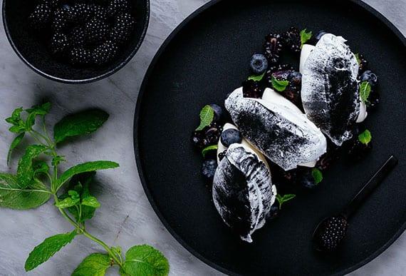 black food rezepte für leckere schwarze desserts_hausgemachter meringe-nachtisch mit aktivkohle und schwarzen beeren auf sahne