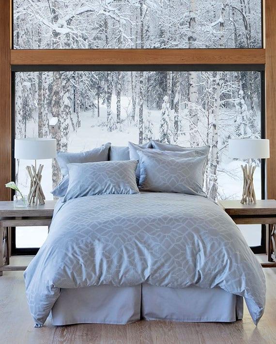 coole einrichtungsidee für gemütliches schlafzimmer im winter mit doppelbett vor panoramafenster mit rechteckigen nachttischen holt, tischlampen aus treibholz und moderne bettwäsche hellgrau