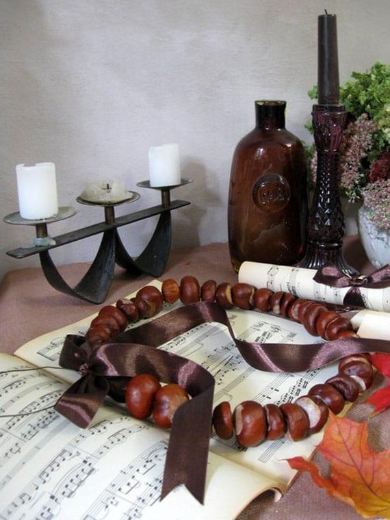 coole dekoidee für herbstliche Sideboard-Deko mit kranz aus kastanien, kerzen,notenheft und herbstpflanzen
