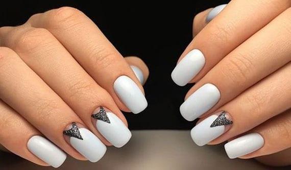 moderne und elegante maniküre mit schwarzen pfeilen auf weiß lackierten nagelplatten