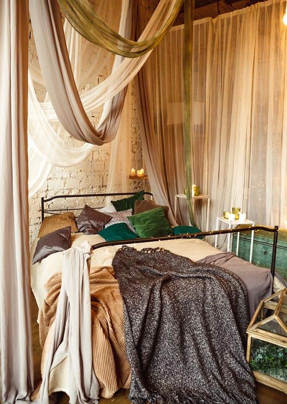 romantisches schlafzimmer im boho wohnstil mit vintage metallbettgestell, baldachin in weiß und beige, weißen beistelltischen mit kerzen, alter holzkomode grün, ziegelwand weiß und kuscheligen bettdecken