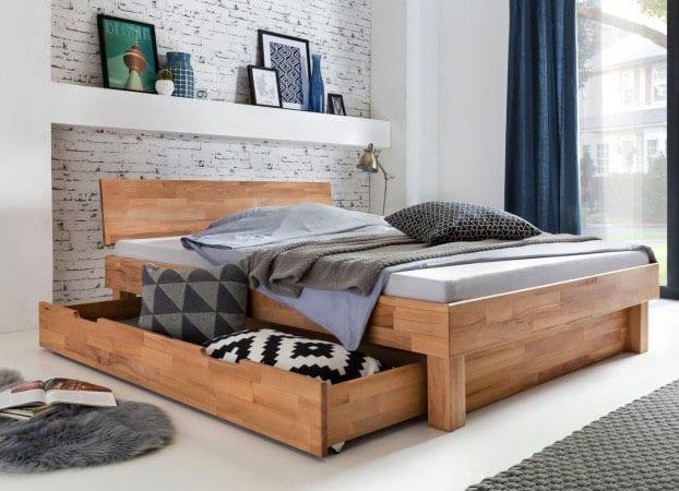 moderne schlafzimmergestaltung mit holzbett in wandnische mit wandregal für dekorartikel, akzentwand mit tapete in ziegeloptik weiß, dunkelblauen gardinen, teppich und bettdecke grau