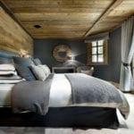 gemütliche rustikale schlafzimmergestaltung mit holzwandverkleidung, grauen wänden, holzdecke und bettbezug in weiß und grau