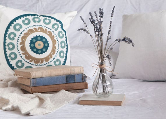 coole schlafzimmer deko im boho chic style mit lavendel in glasvase, paar alten büchern und weißem bettbezug mit floral gemusterten kissen in blau