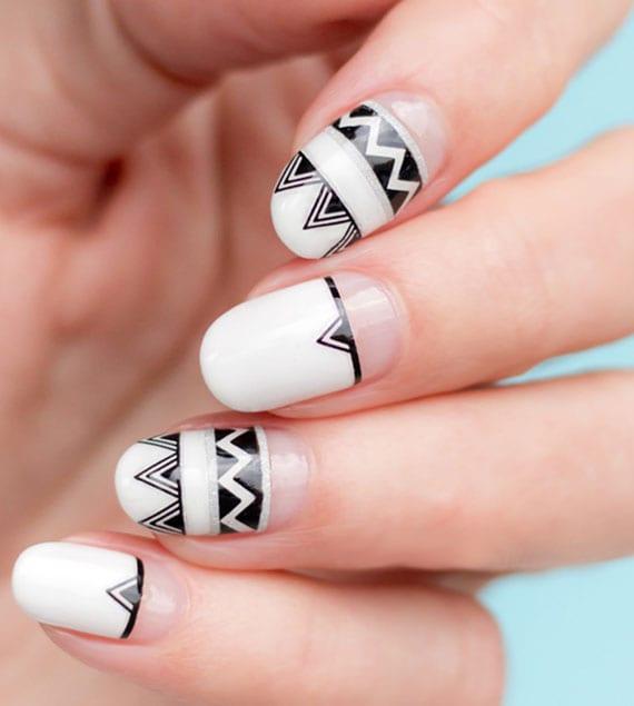 moderne halbmond maniküre in weiß und schwarz mit geometrischen motiven