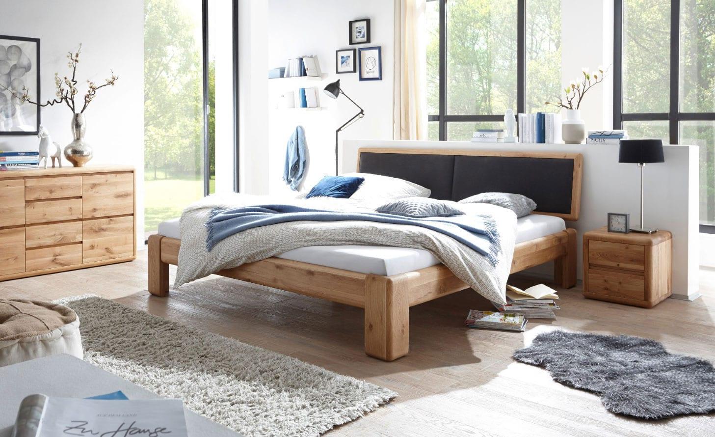 coole ideen für moderne einrichtung schlafzimmer mit doppelbett aus massivholz mit stofkopfteil schwarz, holznachttischen, sideboard holz,schaffell grau, stehlampe schwarz und deko mit frühlingszweigen in vasen