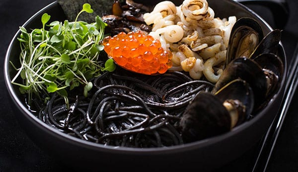 leckeres pasta rezept mit schwarzen spagetti, lachsrugen, microgreens, muscheln, pilzen und kalamaren