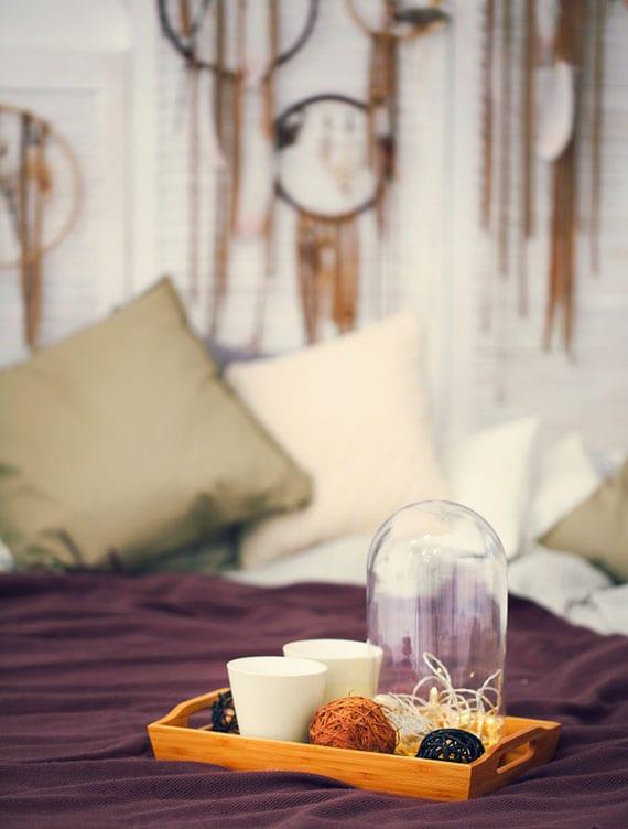diy traumfänger als coole zimmerdeko für schlafzimmer im boho wohnstil mit diy holzbettkopfteil weiß, bettdecke dunkellila, kissen in weiß und beige, holztablett mit glasglocke und dekokugeln