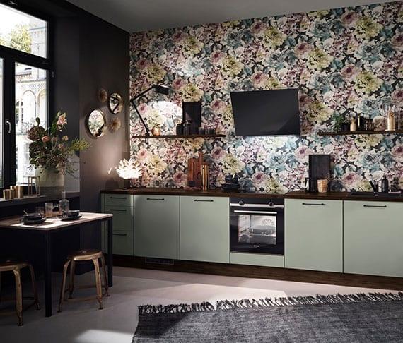 stilvolle und wohnliche küchengestaltung mit floral-tapeten als Akzentwand in rustikaler küche mit holzwandregalen, hellgrünen küchenfronten, wandfarbe schwarz und esstisch mit metallhockern im industriellen stil