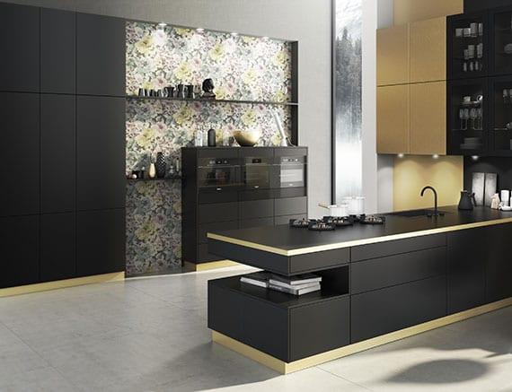 Einrichtungsidee für stilvolle Trendküche in Mattschwarz mit Küchenschränken und Küchensockel in Gold, Betonboden, Akzentwand mit Floral-Wandtapete, Einbauschrankwand schwarz, Wandnische mit wandregalen