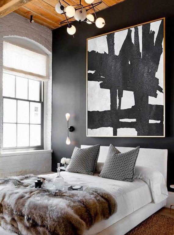 moderne schlafzimmer einrichtung mit weißem bett, designer-lampen, abstraktem acrylgemälde als wanddeko schwarzer wand
