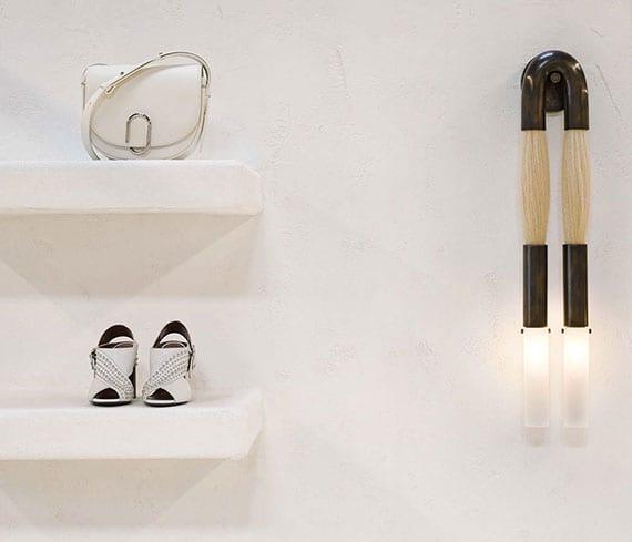 modernes interieur design vom modedesign laden mit weißen ausgemauerten wandregalen und modernen wandleuchten aus schwarzem messing, milchglas und pgerdehaar