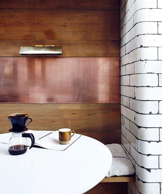 gemütliche sitzecke in kleiner küche einrichten mit rundem esstisch weiß, holzsitzbank, wandverkleidung aus kupfer und holz, akzentwand aus weißen wandfliesen