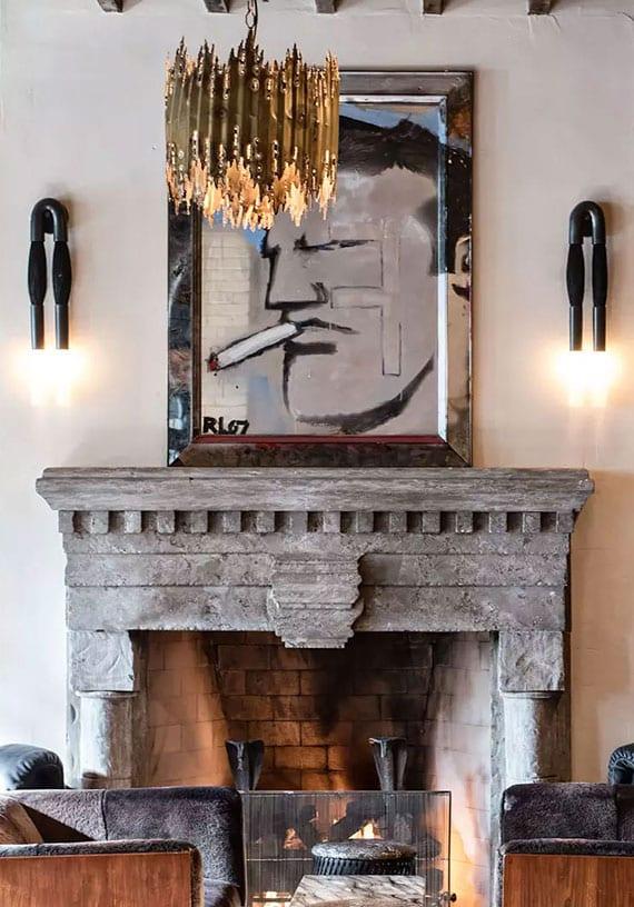 coole wohnzimmer einrichtung mit kaminsims aus grauen kalssteinen, schwarzen wandlampen aus pferdehaar, moderner pendelleuchte in gold, holzsesseln schwarz