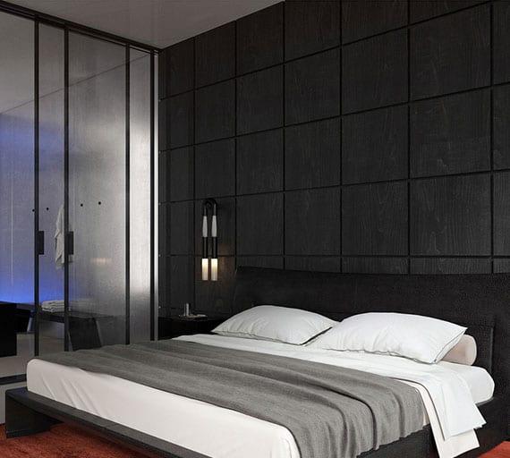 modernes schlafzimmer interieur in schwarz mit holzwandverkleidung, glastüren zum bad, schwarzem bett auf rotem teppich und modernen wandleuchten in schwarz mit weißem pferdehaar