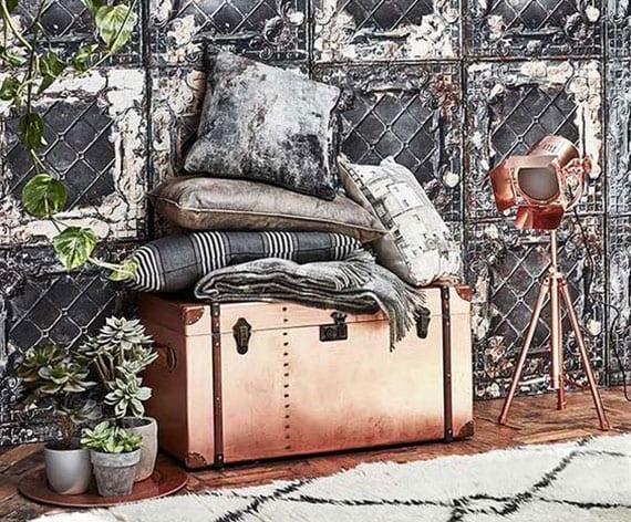 attraktive raumdekoration mit vintage-wandtapete, Sukkulenten in grauen töpfen, grauen dekokissen auf koffer in kupferfarbe
