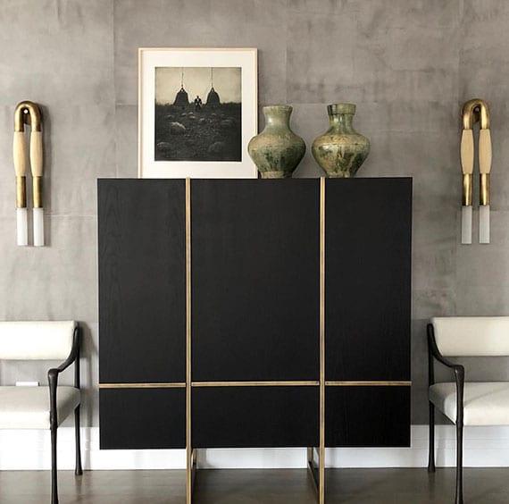 stilvolle wohnesszimmer einrichtung mit schwarzem sideboard, weißen stühlen, modernen wandleuchten aus messing und pferdehaar als akzent zur betonwand